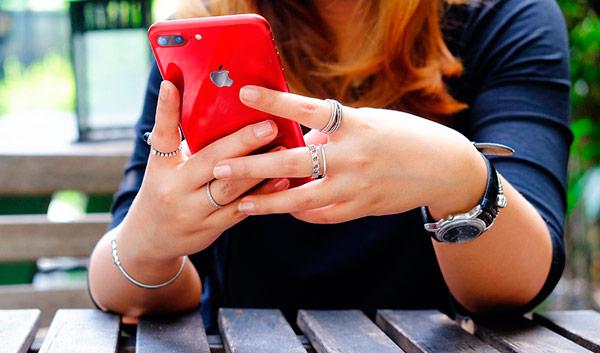 mujer con iphone rojo